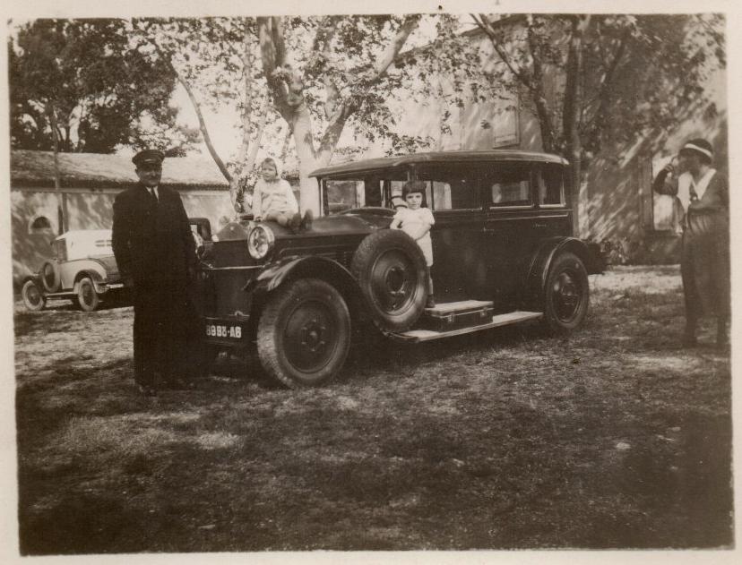 Diese Familie leistet sich eine große Chauffeurslimousine (eventuell den Typ 184) und - im Hintergrund - einen Typ 172 Torpedo